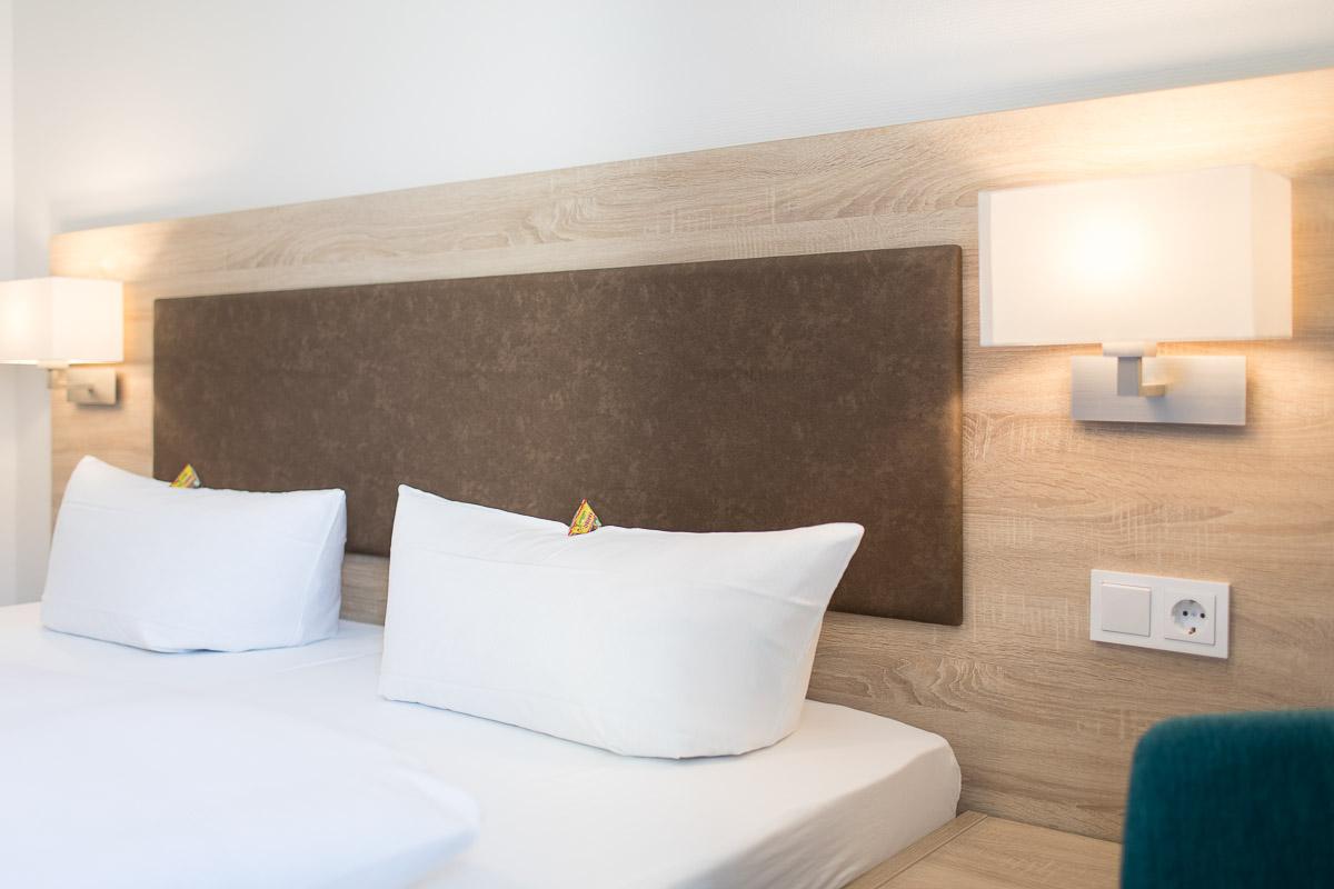 Gemütliches Bett mit großen Kissen im Hotel Pelikan in Beuron