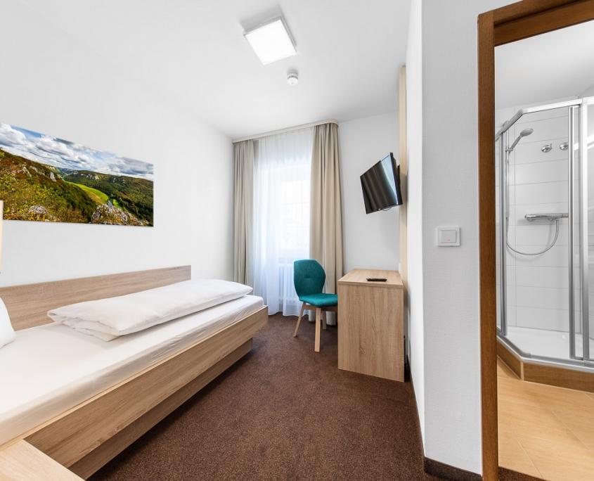 Einzelzimmer mit Bad und Fernseher im Hotel Pelikan in Beuron